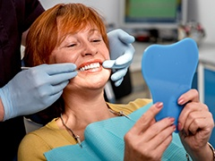 Senior woman in dental chair looking at smile in mirror