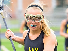 Teen girl playing lacrosse with mouthguard