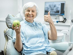 elderly woman giving a thumbs up and holding a green-yellow apple