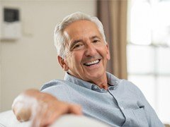 happy elderly man sitting on a couch