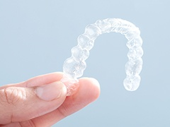 Hand holding clear Invisalign tray