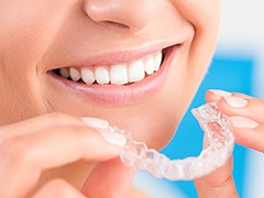 Closeup of smiling patient holding Invisalign tray