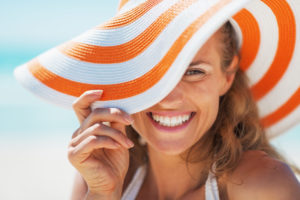 woman smiling behind a floppy hat