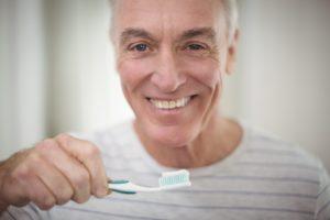 Senior man brushing teeth