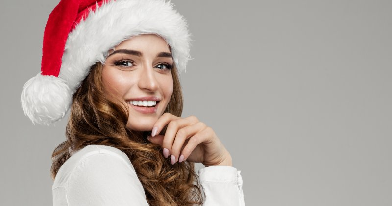 A woman smiling and wearing a Santa hat.