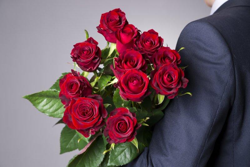 man black suit holding a dozen roses