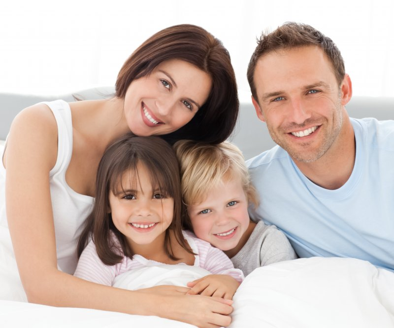 family of four hugging and smiling