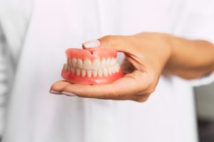 doctor holding dentures in Torrance
