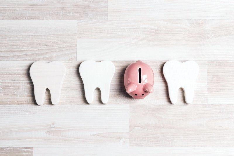 Piggy bank in a row of cardboard teeth