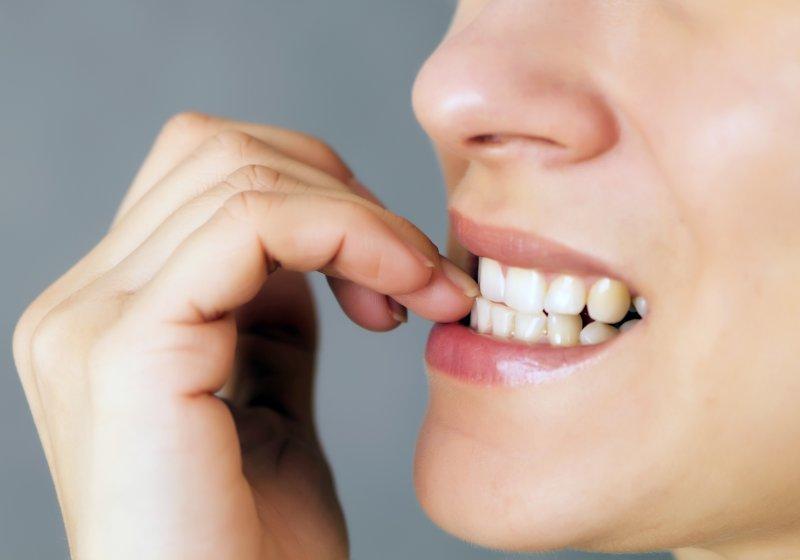 Closeup of woman biting her nails