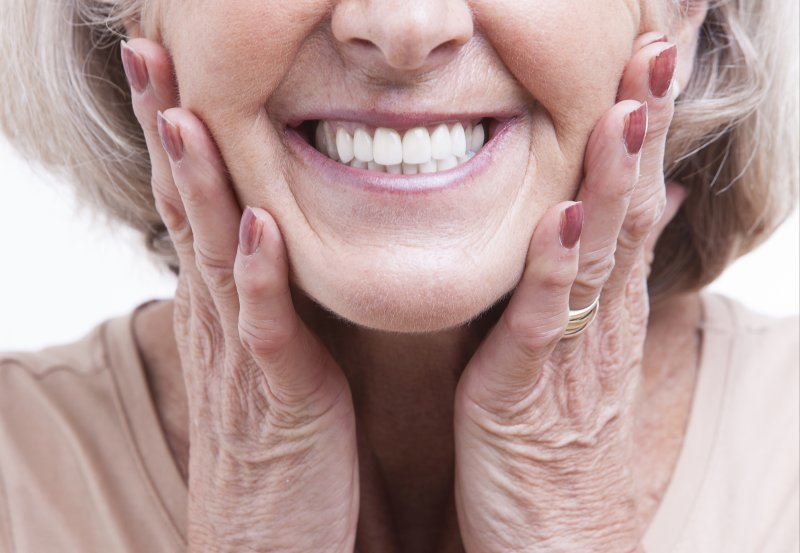 an up-close view of an older woman's smile and her hands holding both sides of her face