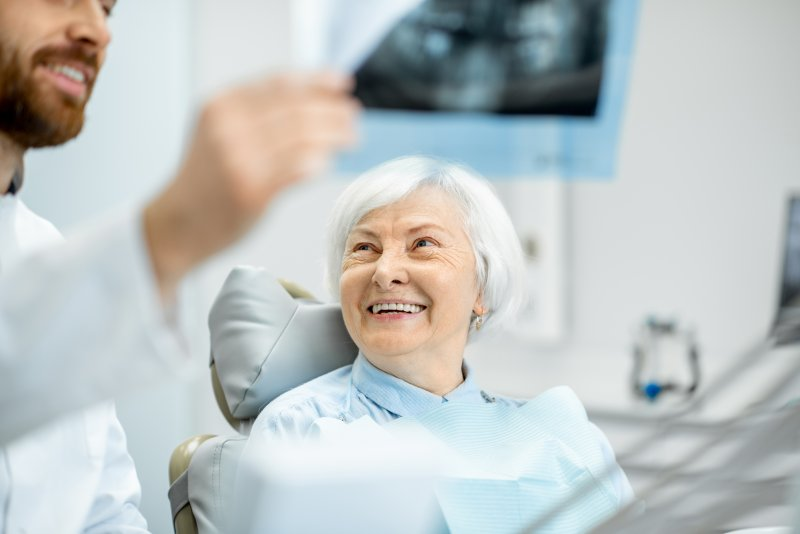 Dentist showing smiling woman her X-rays