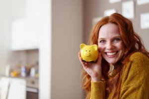 Woman holding piggy bank, used dental financing for cosmetic services