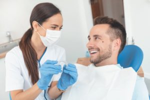Dentist answering male patient's Invisalign questions during consultation